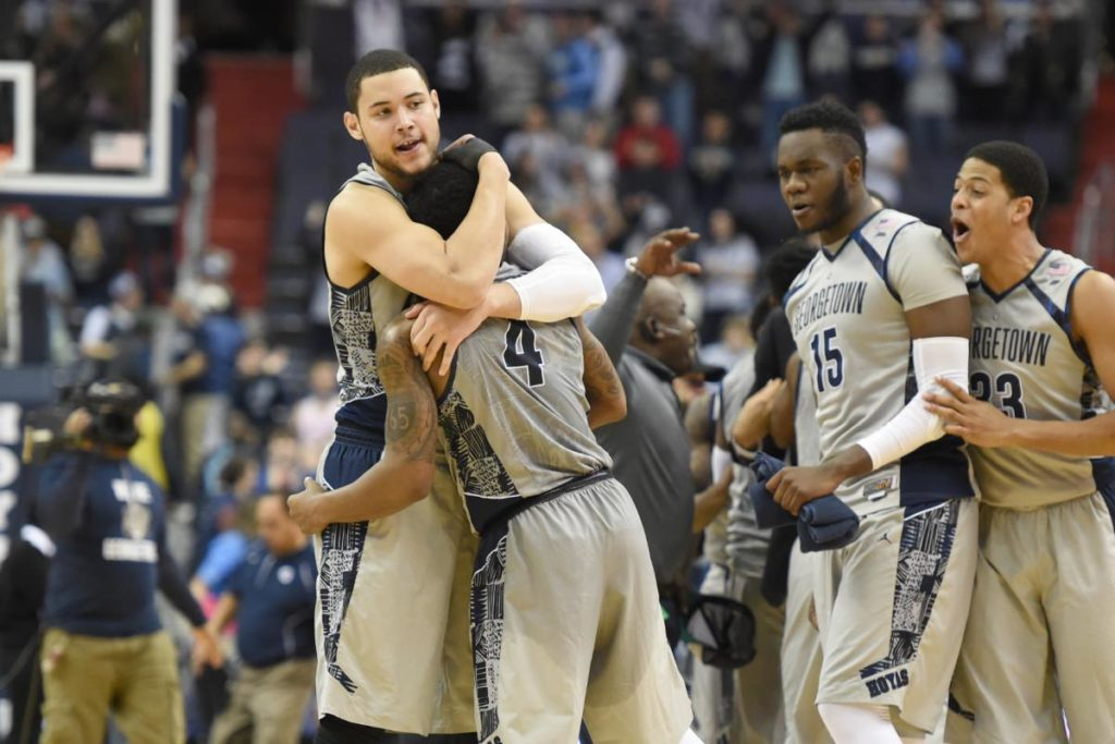 Georgetown Hoyas basketball players celebrate a win on the court of a basketball game.