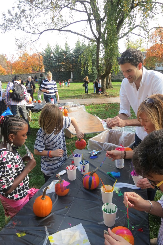 A Georgetown graduate student shows young children how to do an activity at an outdoor event as part of a club-sponsored event.