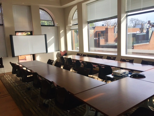 view of the Gradaute School conference room, Car Barn room 427 showing tables and projector screen