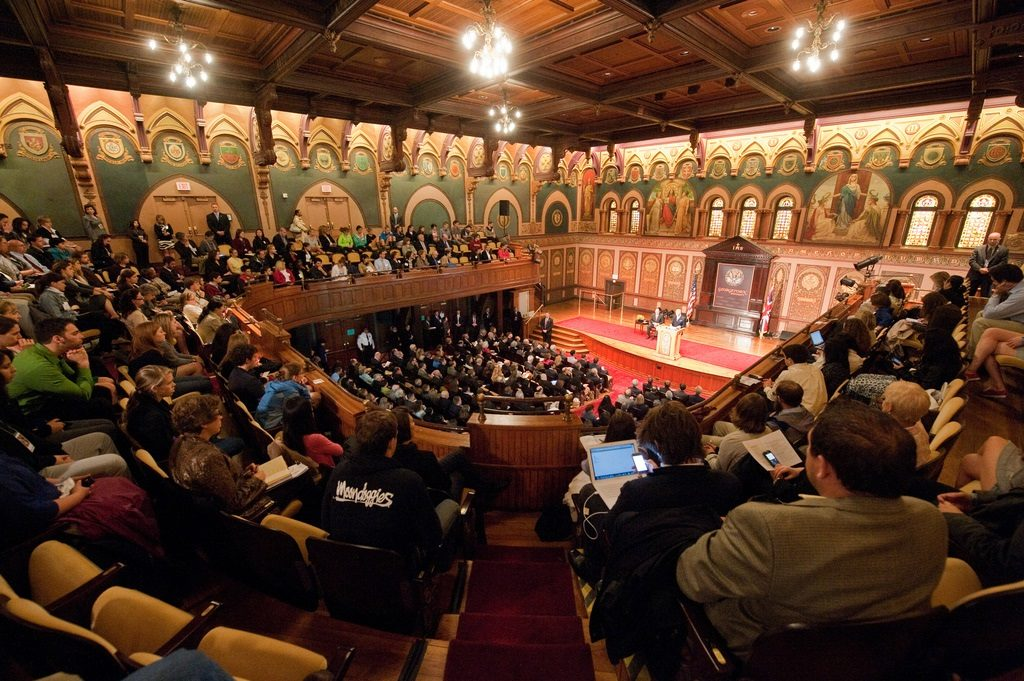 Graduate students and others sitting in a large ornate auditorium - Gaston Hall.